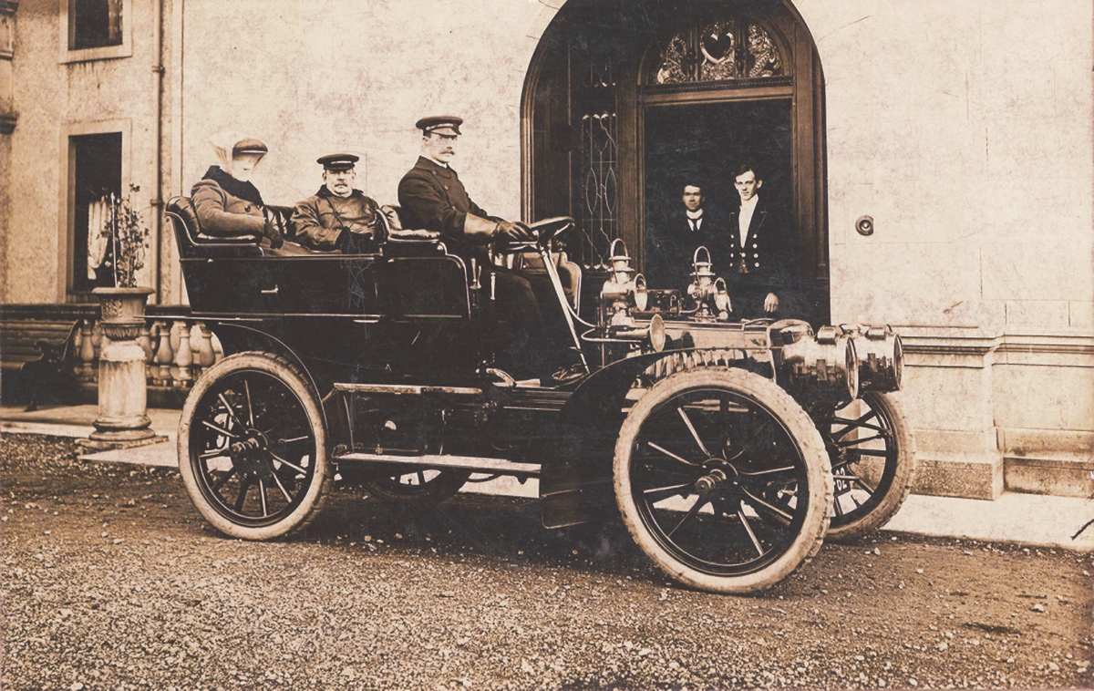 Black and white photograph of Sir Charles and Lady Cayzer, with driver, in their car at Gartmore . Two staff stood in entrance to house.