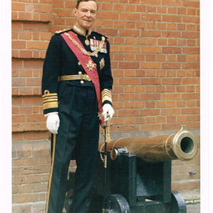 Colour photograph of Admiral Sir Charles Edward Madden in uniform beside a cannon