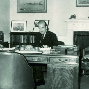 Black and white photograph of Sir Nicholas Cayzer, 2nd Bart., of Roffey Park (as he was then) at his desk in the St. Mary Axe office.