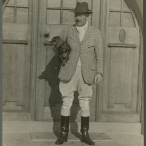 Black and white photograph of Major Harold Stanley Cayzer holding a dog