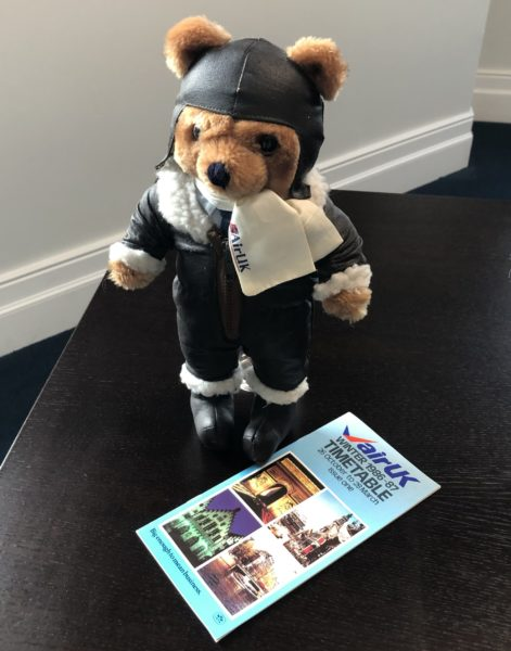 Colour photo of Air UK teddy bear dressed in pilot's uniform, with Air UK printed timetable